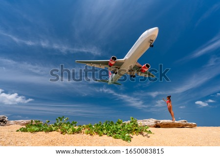 Woman have fun on the beach watching the landing planes. Traveling on an airplane concept. Text spac Stock photo © galitskaya