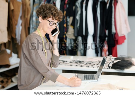 Pretty young owner of fashion designing studio consulting clients Stock photo © pressmaster