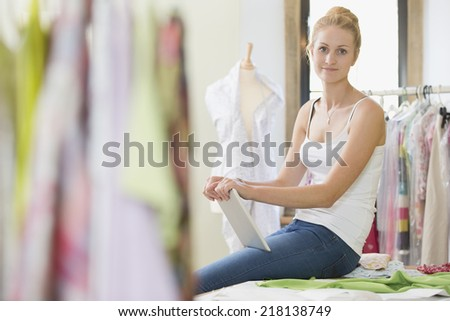 Young creative fashion designer with tablet making digital sketches Stock photo © pressmaster