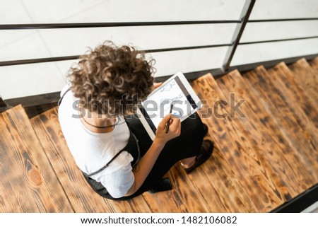 View of young elegant fashion designer pointing at one of new sketches Stock photo © pressmaster