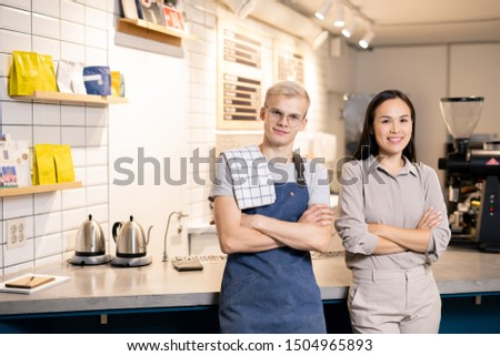 young successful waiters in uniform looking at you while standing by workplace stock photo © pressmaster