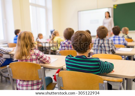 Rear view of schoolkids studying and sitting at desk in classroom of elementary school Stock photo © wavebreak_media
