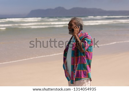 Vista lateral senior homem falante telefone móvel praia Foto stock © wavebreak_media
