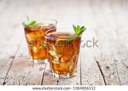 Cold iced tea with lemon, mint leaves and ice cubes in two glass Stock photo © marylooo