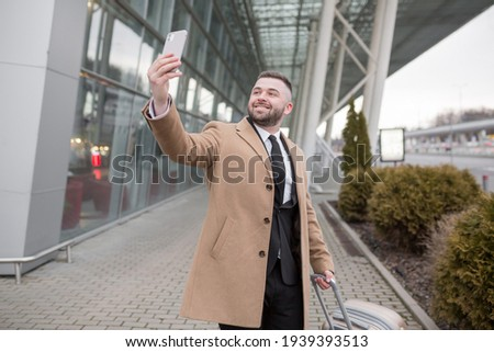 Serious bald mature businessman with smartphone looking at you in airport lobby Stock photo © pressmaster