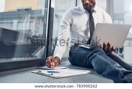 Young serious male employee making notes in notebook while organizing work Stock photo © pressmaster