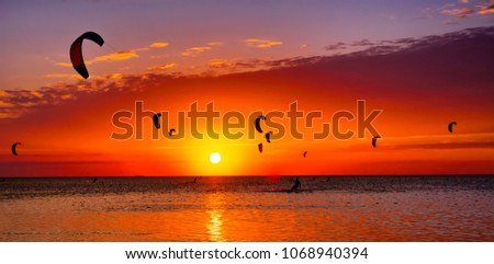 Many colorful kites on beach and kite surfers riding waves during windy day Stock photo © ruslanshramko