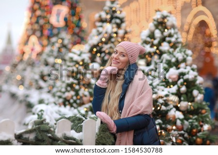 Close-up of a blonde in mittens and a scarf against the background of New Year's city trees Stock photo © ElenaBatkova