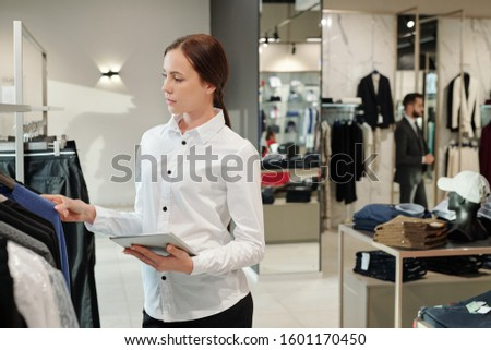 Pretty young elegant consultant of contemporary boutique using tablet Stock photo © pressmaster