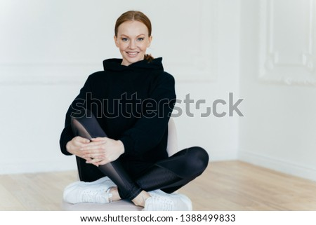 Relaxed cheerful woman in black sweatshirt, sits in lotus pose on chair, sits indoor, has glad expre Stock photo © vkstudio