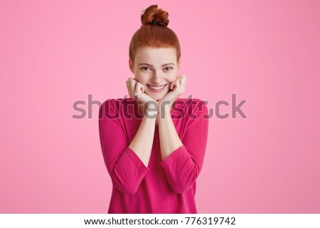 Headshot of attractive woman keeps hands under chin, has ginger hair, pleasant toothy smile, wears y Stock photo © vkstudio