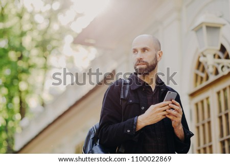 Outdoor view of thoughtful male tourist carries rucksack, holds modern smart phone in hands as tries Stock photo © vkstudio