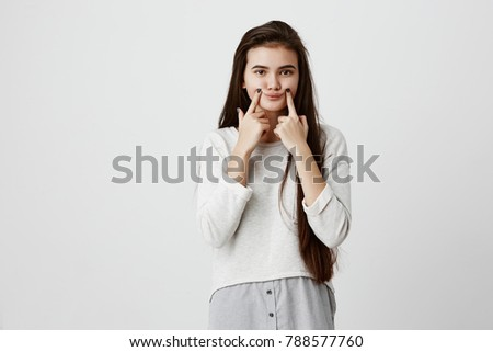 Waist up portrait of thoughtful female with dark straight long hair, keeps hand under chin, contempl Stock photo © vkstudio