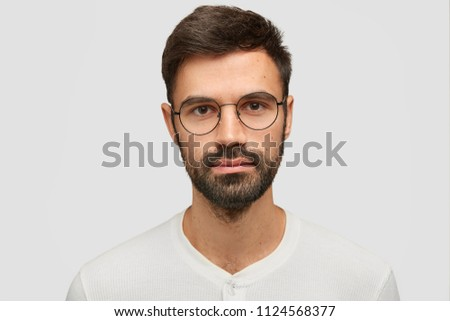 Headshot of handsome man with thick beard and mustache, has secret look, demonstrates silence sign,  Stock photo © vkstudio