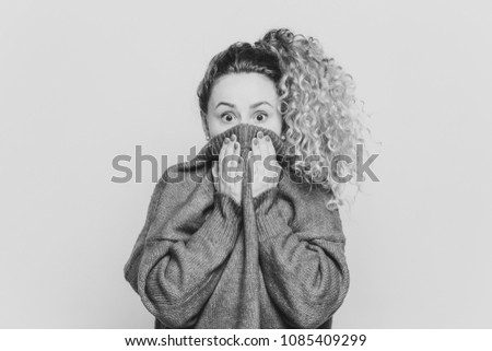 Frightened stunned female sees her phobia, covers face with collar of red sweater, stares at camera  Stock photo © vkstudio