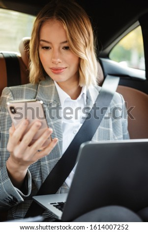 Image of businesslike woman using laptop inside car on passenger Stock photo © deandrobot