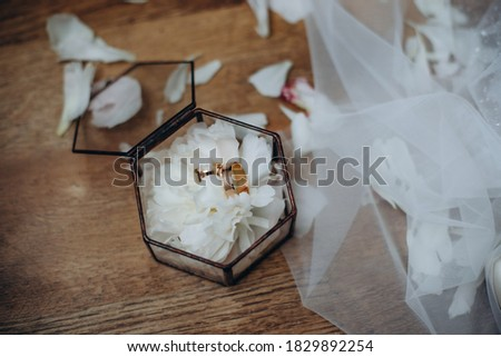 on the glass table in the room is a box with wedding rings, next to it is a bouquet of flowers Stock photo © ruslanshramko