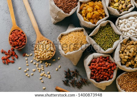 Husbandry and nutrtion concept. Top view of various beans and colorful dried fruit packed in little  Stock photo © vkstudio