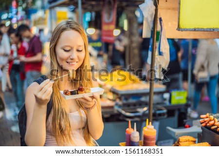 Young woman tourist eating Typical Korean street food on a walking street of Seoul. Spicy fast food  Stock photo © galitskaya