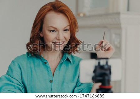Pleased redhead young European woman uses front cellphone camera on tripod, has personal vlog, shoot Stock photo © vkstudio