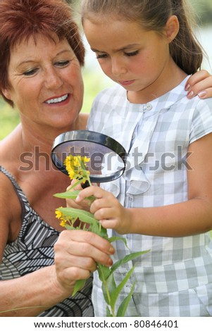 a 55 years old woman and a little looking a yellow flower with a magnifying glass Stock photo © photography33