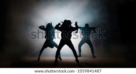 A group of female freestyle hip-hop dancers in a dancing training session. Lit with spotlights. Move Stock photo © Forgiss