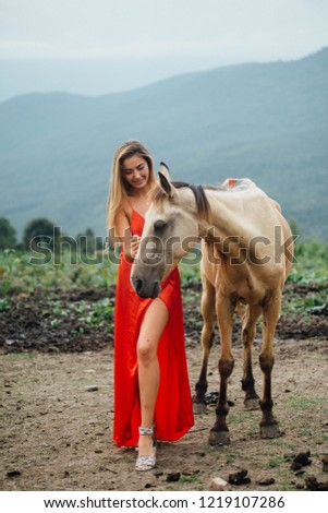 Stok fotoğraf: Gorgeous Blonde Woman Riding A Horse In Fashionable Red Dress