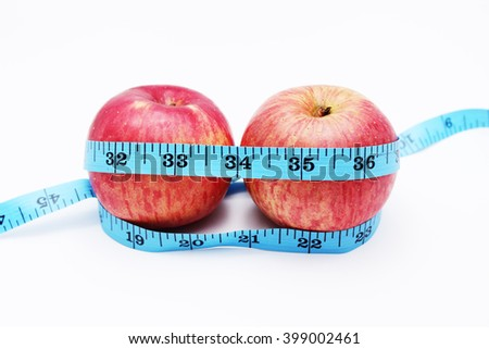 Stock photo:  tape measure wrapped around the apple isolated on white backgro