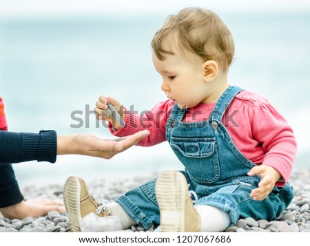 little girl sits on beach at water edge in autumn day and feeds pigeons stock photo © paha_l