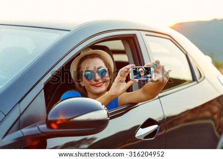 Young woman in sunglasses making self portrait sitting in the ca Stock photo © vlad_star