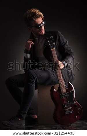 dramatic young guitarist looking back while holding guitar on sh stock photo © feedough