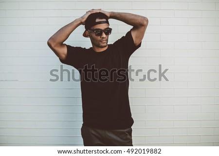 Nyugodt fiatalember fekete ruházat áll tart Stock fotó © feedough