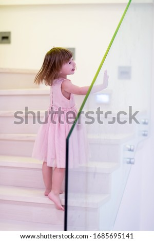 adorable little girls is laughing while standing on wooden chair Stock photo © feedough