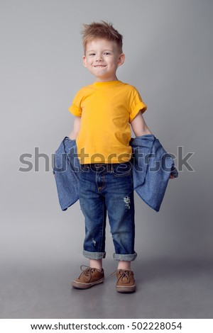 Portrait of cute little blonde caucasian boy in yellow t-shirt hoping asking for forgiveness on gray Stock photo © Traimak