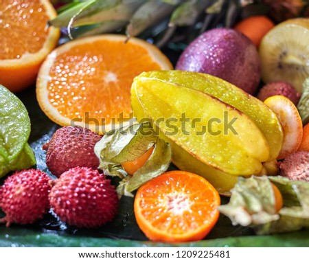 Close-up of tropical fruits - carambola, litchi, coconut, pineapple on a gray stone table. Stock photo © artjazz