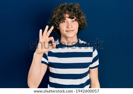 Young man in striped t-shirt smiling and showing ok sign while t Stock photo © deandrobot