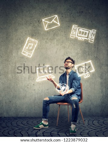 skillful man sitting on chair and juggling with electronic devices icons Stock photo © ichiosea