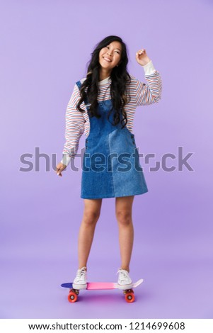 happy cute asian woman posing isolated over purple wall background with skateboard stock photo © deandrobot