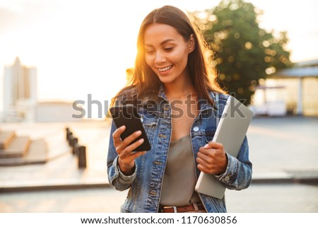 Beautiful woman student walking in park holding laptop listening music. Stock photo © deandrobot