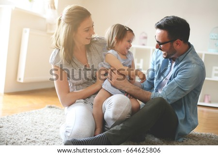 smiling young family with little baby girl spending time together stock photo © deandrobot