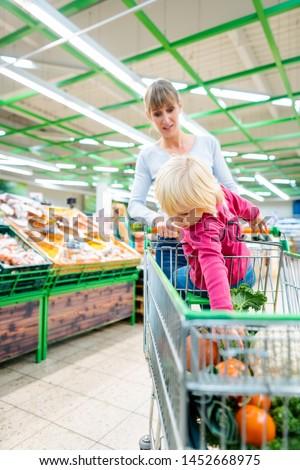 Mother having her toddler riding in shopping card of supermarket Stock photo © Kzenon