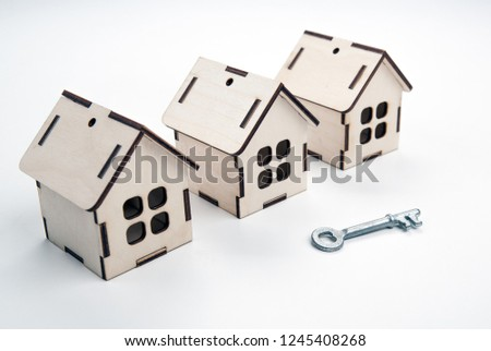 three wooden miniature houses and a door key on a wooden backgro Stock photo © mizar_21984