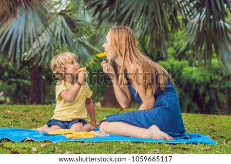 Mom and son had a picnic in the park. Eat healthy fruits - mango, pineapple and melon. Children eat  Stok fotoğraf © galitskaya