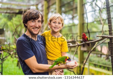 Dad and son feed the parrot in the park. Spending time with kids Stock photo © galitskaya