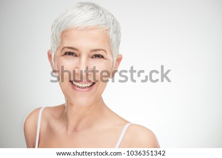 Happy senior female with short white hair looking at beautician Stock photo © pressmaster