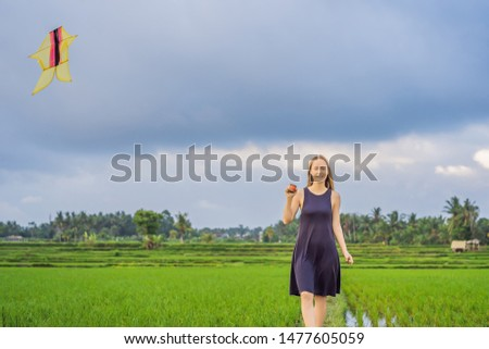 young woman launches a kite in a rice field in ubud bali island stock photo © galitskaya