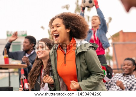 Ecstatic intercultural friends cheering for their football team after goal Stock photo © pressmaster