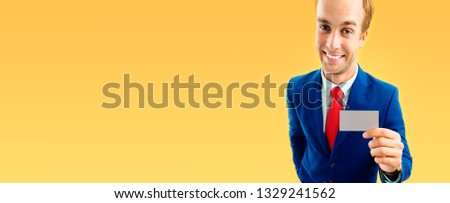 Stock photo: Businessman in blue suit and with a red tie, shows business card