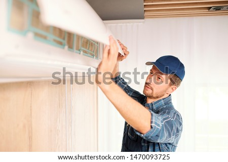 Young electrician or repiar service technician opening lid of air conditioner Stock photo © pressmaster