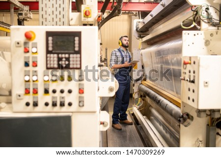 Young factory engineer in workwear testing new production system or technology Stock photo © pressmaster
